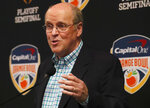 FILE - College Football Playoff executive director Bill Hancock gestures as he speaks during a news conference before an NCAA college football game between Miami and North Carolina in Miami Gardens, Fla., in this Thursday, Sept. 27, 2018, file photo. The CFP would expand from four to 12 teams, with six spots reserved for the highest ranked conference champions, under a proposal that will be considered next week by the league commissioners who manage the postseason system,  a person familiar with announcement told The Associated Press on Thursday, June 10, 2021. The person spoke on condition of anonymity because the CFP has not yet released details. (AP Photo/Wilfredo Lee, File)