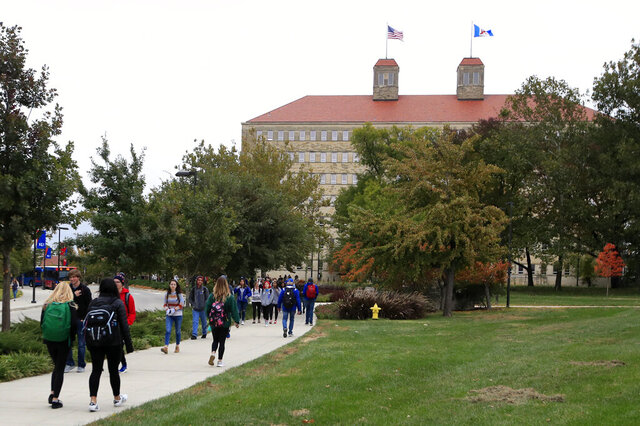 FILE - In this Oct. 24, 2019, file photo students walks in front of Fraser Hall on the University of Kansas campus in Lawrence, Kan. Many parents take out student loans to help pay for their child's education. But not all of them share that information with their son or daughter. That silence is an easy misstep for parents who decide to borrow student loans in their own names.  (AP Photo/Orlin Wagner, File)
