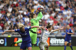 Chelsea's goalkeeper Ann-Katrin Berger, center, catches the ball during a challenge with Lyon's Lucy Bronze, right, during their Women's Champions League semifinal soccer match in Decines, France, Sunday, April 21, 2019. (AP Photo/Laurent Cipriani)