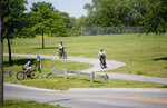 FILE - In this May 15, 2020, file photo, cyclists use the Lick Run Greenway at Washington Park in Roanoke, Va. In the sporting goods industry, the impact has depended on the focus of the business. Companies selling bikes and cycling equipment have had a hard time keeping up with the demand, with sales of adult leisure bikes up 121% in March and children's and BMX bikes up 56%. (Stephanie Klein-Davis/The Roanoke Times via AP, Fle)