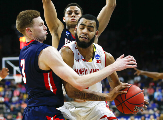 Maryland 's Eric Ayala, front right, tires to get away from Belmont 's Dylan Windler, left, and Kevin McClain, back, during the first half of a first round men's college basketball game in the NCAA Tournament in Jacksonville, Fla., Thursday, March 21, 2019. (AP Photo/Stephen B. Morton)