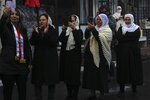 Druze women look at Sidqi al-Maq and Amal Abu Saleh upon their release from Israeli prison in the village of Majdal Shams on the border with Syria Friday, Jan. 10, 2020. (AP Photo/Ariel Schalit)