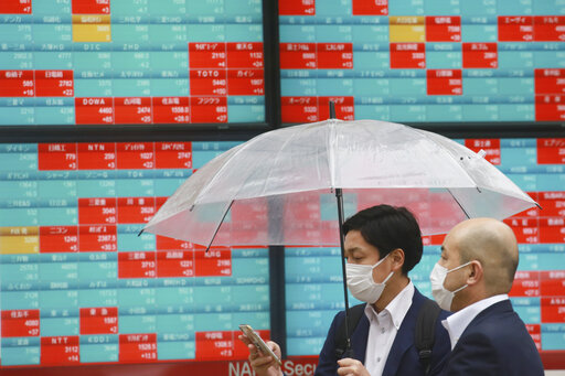 People walk by an electronic stock board of a securities firm in Tokyo, Wednesday, Oct. 13, 2021. Shares were mixed in Asia on Wednesday after an up-and-down day on Wall Street ended with most benchmarks lower as traders waited for updates on inflation and corporate  earnings. (AP Photo/Koji Sasahara)