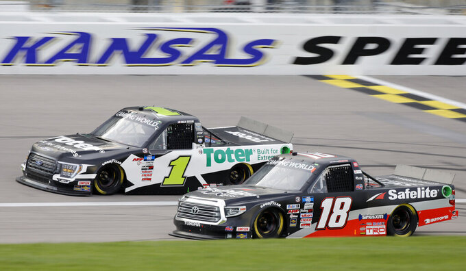 Hailie Deegan (1) passes Chandler Smith (18) during a NASCAR Truck Series auto race at Kansas Speedway in Kansas City, Kan., Saturday, May 1, 2021. (AP Photo/Colin E. Braley)