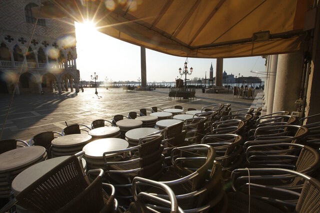 FILE - In this Monday, April 6, 2020 file photo, chairs and tables are piled in front of a bar in St. Mark's Square, in Venice during a lockdown to prevent the spread of the coronavirus. The coronavirus outbreak is straining social safety nets across the globe - and underlining sharp differences in approach between wealthy societies such as the United States and Europe. In Europe, the collapse in business activity is triggering wage support programs that are keeping millions on the job, for now.   (AP Photo/Andrew Medichini, File)