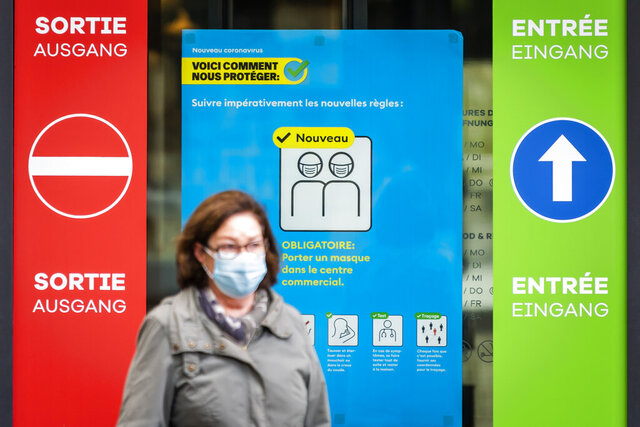 "A woman wearing a protective mask walks in front of a FOPH poster in front of a shopping centre in Fribourg, Switzerland, Friday, Oct. 16, 2020. Europe is at a ""turning point"" in the fight against the coronavirus, said Bertrand Levrat, head of Switzerland's biggest hospital complex, acknowledging growing public fatigue over anti-COVID measures but says people must buckle down as Switzerland grapples with record daily case counts with measures like limiting the size of gatherings and stripping soldiers of weekend leave. (Jean-Christophe Bott/Keystone via AP)"