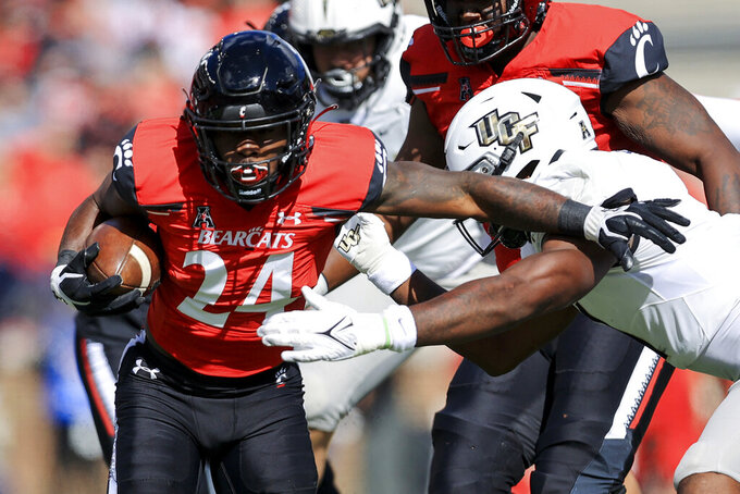 Cincinnati running back Jerome Ford (24) carries the ball as he breaks a tackle against UCF linebacker Jeremiah Jean-Baptiste, right, during the first half of an NCAA college football game, Saturday, Oct. 16, 2021, in Cincinnati. (AP Photo/Aaron Doster)