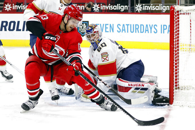 Carolina Hurricanes' Warren Foegele (13) tries to control the puck and shoot it at Florida Panthers' goaltender Chris Driedger (60) during the second period of an NHL hockey game in Raleigh, N.C., Sunday, March 7, 2021. (AP Photo/Karl B DeBlaker)