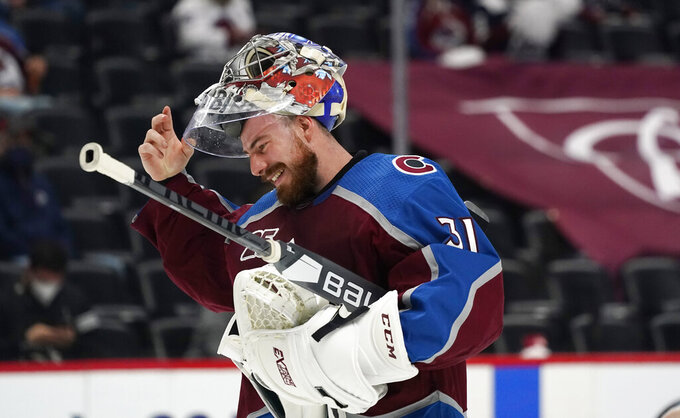 Colorado Avalanche goaltender Philipp Grubauer jokes with teammates during a timeout in the first period of Game 2 of an NHL hockey Stanley Cup first-round playoff series against the St. Louis Blues on Wednesday, May 19, 2021, in Denver. (AP Photo/David Zalubowski)