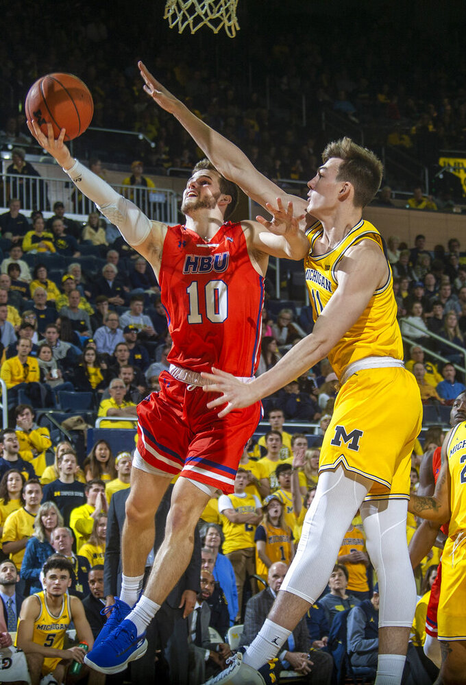Houston Baptist guard Ty Dalton (10) shoots as Michigan forward Colin Castleton defends during the first half of an NCAA college basketball game in Ann Arbor, Mich., Friday, Nov. 22, 2019. (AP Photo/Tony Ding)