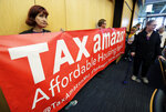 Demonstrators opposing the repeal of a tax on large companies such as Amazon and Starbucks that was intended to combat a growing homelessness crisis hold a sign that reads