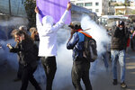 Activists react to crowd control projectiles fired by Israeli police during a protest against planned evictions in east Jerusalem, Friday, April 9, 2021. (AP Photo/Mahmoud Illean)