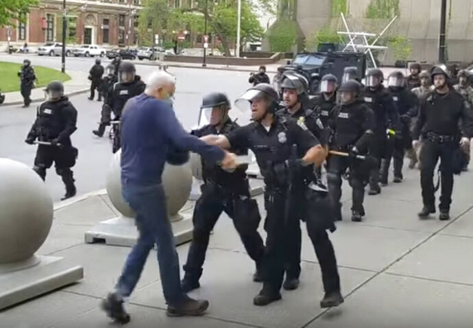 "In this image from video provided by WBFO, a Buffalo police officer appears to shove a man who walked up to police Thursday, June 4, 2020, in Buffalo, N.Y. Video from WBFO shows the man appearing to hit his head on the pavement, with blood leaking out as officers walk past to clear Niagara Square. Buffalo police initially said in a statement that a person ""was injured when he tripped & fell,"" WIVB-TV reported, but Capt. Jeff Rinaldo later told the TV station that an internal affairs investigation was opened. Police Commissioner Byron Lockwood suspended two officers late Thursday, the mayor's statement said. (Mike Desmond/WBFO via AP)"