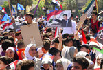 In this photo released by the Syrian official news agency SANA, protesters wave flags and a portrait of President Bashar Assad, as they march during a demonstration to show solidarity with the Syrian armed forces, at Omayyad Square, in Damascus, Syria, Monday, April 16, 2018. Hundreds of Syrians have gathered in a landmark square in the capital of Damascus in support of their armed forces, which they say succeeded in confronting the unprecedented joint airstrikes by the West over the weekend. (SANA via AP)