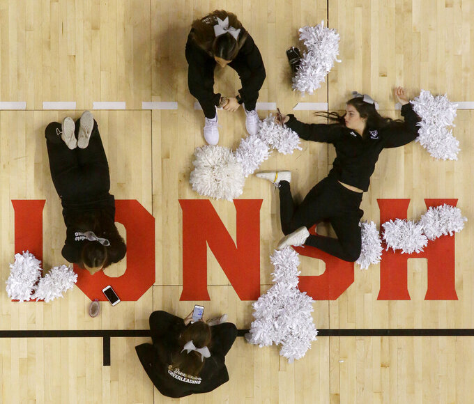 St. Bonaventure cheerleaders lounge on the baseline prior to an NCAA college basketball final game against Saint Louis in the Atlantic 10 men's tournament, Sunday, March 17, 2019, in New York. (AP Photo/Julio Cortez)