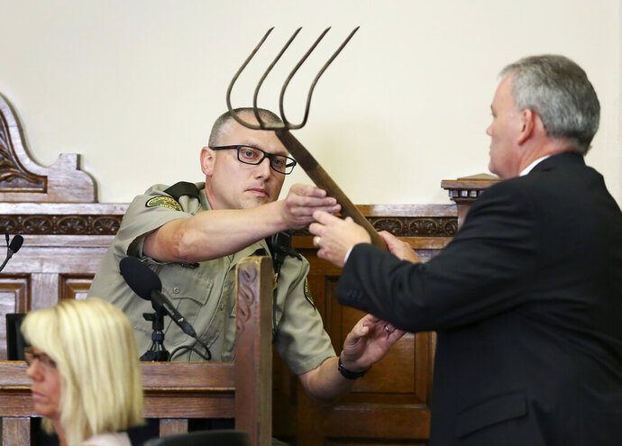 Delaware County's county attorney John Bernau, right, questions witness Delaware County Deputy Eric Holub as he hands back a corn rake during the first-degree murder trial for Todd Mullis at Dubuque County Courthouse in Dubuque, Iowa, on Tuesday, Sept. 17, 2019. Todd Mullis is accused of killing Amy L. Mullis by stabbing her with that rake on Nov. 10.  (Nicki Kohl/Telegraph Herald via AP)