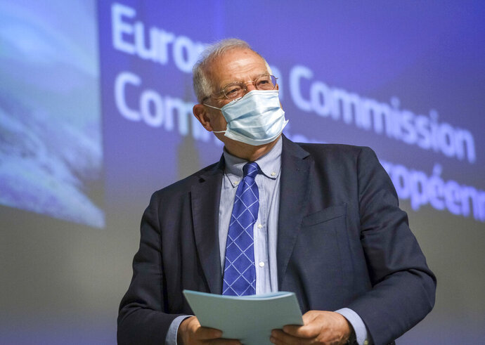 EU foreign policy chief Josep Borrell, wearing a face mask, leaves at the end of a video press conference following the International Donors' Conference in solidarity with Venezuelan refugees and migrants at the EU headquarters in Brussels, Tuesday, May 26, 2020. International donors on Tuesday pledged more than 2.5 billion euros ($2.7 billion) in support for refugees and migrants from Venezuela as the coronavirus pandemic deepens their plight. (Olivier Hoslet, Pool Photo via AP)