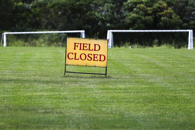 A sign announces that the field is closed at Vernon Hills Athletic Complex in Vernon Hills, Ill., Thursday, July 30, 2020. Governor J.B Pritzker introduced new restrictions for recreational sports leagues in Illinois Wednesday, as the number of coronavirus cases continues to rise across the state. (AP Photo/Nam Y. Huh)