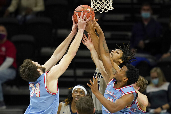 Lewis-Clark State forward Jake Albright (34) and guard Damek Mitchell, right, rebounds against Shawnee State forward Latavious Mitchell, back, during the first half of an NAIA basketball game in the finals of the national tournament in Kansas City, Mo., Tuesday, March 23, 2021. (AP Photo/Orlin Wagner)