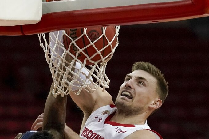 Wisconsin's Micah Potter dunks during the first half of an NCAA college basketball game against Rhode Island Wednesday, Dec. 9, 2020, in Madison, Wis. (AP Photo/Morry Gash)