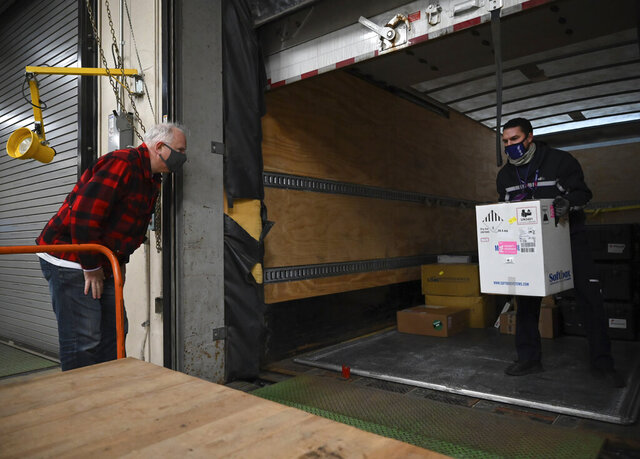 Minnesota Gov. Tim Walz inspects the first delivery of the Pfizer-BioNTech COVID-19 vaccines to the Minneapolis VA Hospital as FedEx driver Seth Warnecke carries the box, Monday, Dec. 14, 2020. (Aaron Lavinsky/Star Tribune via AP, Pool)
