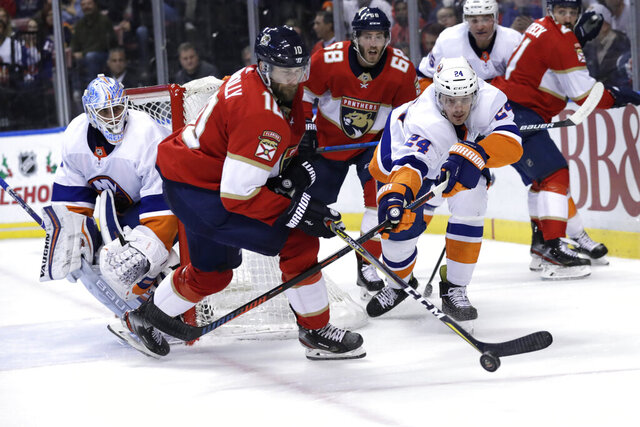 Florida Panthers right wing Brett Connolly (10) and New York Islanders defenseman Scott Mayfield (24) fight for the puck during the second period of an NHL hockey game, Thursday, Dec. 12, 2019, in Sunrise, Fla. (AP Photo/Lynne Sladky)