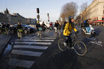 Parisians ride bicycles Tuesday, Dec. 10, 2019 in Paris. Only about a fifth of French trains ran normally Tuesday, frustrating tourists finding empty train stations, and most Paris subways were at a halt. French airport workers, teachers and others joined nationwide strikes Tuesday as unions cranked up pressure on the government to scrap changes to the national retirement system. (AP Photo/Francois Mori)