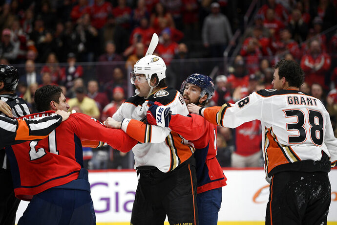 Washington Capitals right wing Garnet Hathaway (21) scuffles with Anaheim Ducks defenseman Erik Gudbranson, second from left, during the second period of an NHL hockey game, Monday, Nov. 18, 2019, in Washington. Also seen is Capitals center Chandler Stephenson, second from right, and Ducks center Derek Grant (38). (AP Photo/Nick Wass)