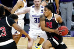 Nebraska guard Shamiel Stevenson, right, drives against Northwestern forward Pete Nance, left, and forward Robbie Beran, center, during the first half of an NCAA college basketball game in Evanston, Ill., Sunday, March 7, 2021. (AP Photo/Nam Y. Huh)