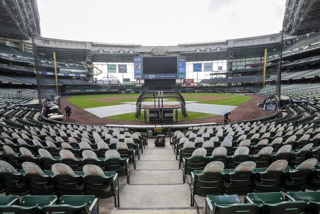 Fan cutouts are seen behind home plate at Miller Park after it was announced that the Milwaukee Brewers home opener was postponed after two St. Louis Cardinals employees tested positive for the coronavirus, Friday, July 31, 2020, in Milwaukee. (AP Photo/Morry Gash)