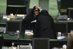 A lawmaker adjusts her veil as she talks with a colleague during the inauguration of Iran's new parliament, in Tehran, Iran, Wednesday, May, 27, 2020. Iran has convened its newly elected parliament, dominated by conservative lawmakers and under strict social distancing regulations, as the country struggles to curb the spread of coronavirus that has hit the nation hard. Iran is grappling with one of the deadliest outbreaks in the Middle East. (AP Photo/Vahid Salemi)