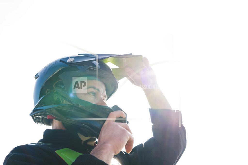 Portrait of motocross driver putting on helmet at sunset