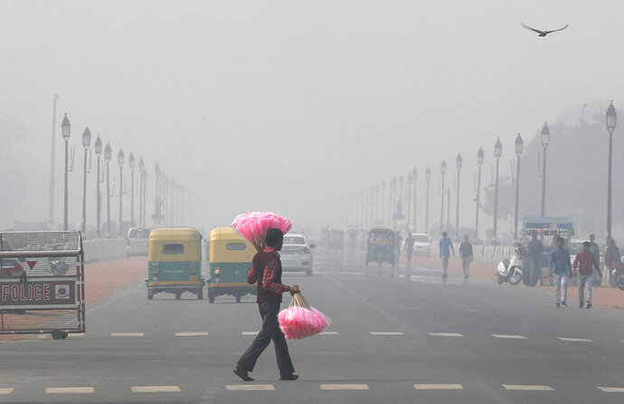 A sweet candy vendor walks amidst thick layer of smog as he looks for customers in New Delhi, India, Tuesday, Nov. 12, 2019. A thick haze of polluted air is hanging over India's capital, with authorities trying to tackle the problem by sprinkling water to settle dust and banning some construction. The air quality index exceeded 400, about eight times the recommended maximum. (AP Photo/Manish Swarup)