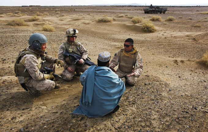 FILE - In this Friday, Dec. 11, 2009, file photo, United States Marine Sgt. Isaac Tate, left, and Cpl. Aleksander Aleksandrov, center, interview a local Afghan man with the help of a translator from the 2nd MEB, 4th Light Armored Reconnaissance Battalion on a patrol in the volatile Helmand province of southern Afghanistan. More than 200 Afghans were due to land Friday in the United States in the first of several planned evacuation flights for former translators and others as the U.S. ends its nearly 20-year war in Afghanistan. (AP Photo/Kevin Frayer, File)