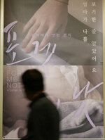 """A visitor walks past a poster of film """"Forget Me Not,"""" at a movie theater in Seoul, South Korea on June 4, 2021. The shock and grief of mother-child separations and intense fear of social stigma captured in """"Forget Me Not"""" offer insight into what's possibly preventing the Danish filmmaker and thousands of other Korean adoptees from reconnecting with their silenced birth mothers, decades after they were jetted to the West. (AP Photo/Lee Jin-man)"""