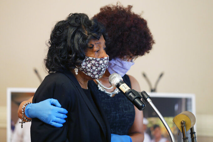 FILE - In this April 22, 2020, file photo, Lillian P. Hammond, foreground, is comforted by her sister-in-law Lori Adams as she speaks at the funeral for her husband, Larry Hammond, who died from the coronavirus, in New Orleans. (AP Photo/Gerald Herbert, File)