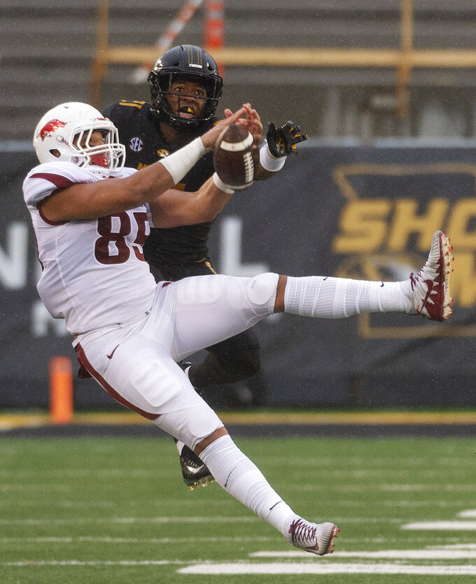 Arkansas tight end Cheyenne O'Grady, left, has the ball knocked away by Missouri's Christian Holmes, right, during the first half of an NCAA college football game Friday, Nov. 23, 2018, in Columbia, Mo. (AP Photo/L.G. Patterson)