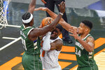 Orlando Magic forward Dwayne Bacon, center, tries to get off a shot between Milwaukee Bucks guard Jrue Holiday, left, and forward Giannis Antetokounmpo (34) during the second half of an NBA basketball game, Monday, Jan. 11, 2021, in Orlando, Fla. (AP Photo/John Raoux)