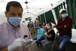 Family members wait in hopes of receiving news of their hospitalized loved ones, in a tent outside a public hospital treating both COVID-19 and other patients, in the Iztapalapa district of Mexico City, Tuesday, May 5, 2020. Iztapalapa has the most confirmed cases of the new coronavirus within Mexico's densely populated capital, itself one of the hardest hit areas of the country with thousands of confirmed cases and around 500 deaths.(AP Photo/Rebecca Blackwell)