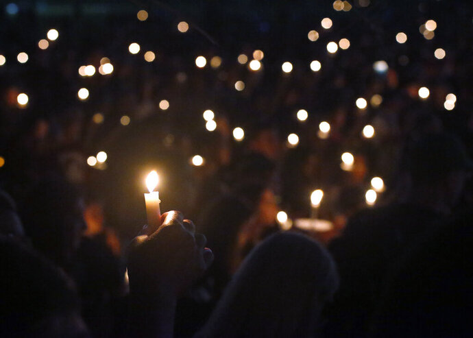 FILE - In this Thursday, Feb. 15, 2018, file photo, attendees hold up their candles at a candlelight vigil for the victims of the shooting at Marjory Stoneman Douglas High School, in Parkland, Fla. A Florida law that allows judges to bar anyone deemed dangerous from possessing firearms has been used 3,500 times since its enactment after the 2018 high school massacre. An Associated Press analysis shows the law is being used unevenly around the state. (AP Photo/Wilfredo Lee, File)