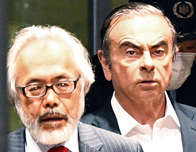 FILE - In this April 25, 2019, file photo, former Nissan Chairman Carlos Ghosn, right, walks behind his lawyer Takashi Takano as he leaves the Tokyo Detention Center in Tokyo. Takano said Saturday, Jan. 4, 2020, he felt outraged and betrayed by his client's escape from Japan to Lebanon, but also expressed an understanding for his feelings of not being able to get a fair trial.