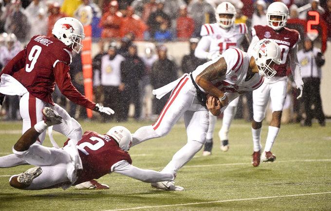 Mississippi quarterback Jordan Ta'amu slips past Arkansas defender Kamren Curl to score a touchdown in the first half of an NCAA college football game Saturday, Oct. 13, 2018, in Little Rock, Ark. (AP Photo/Michael Woods)