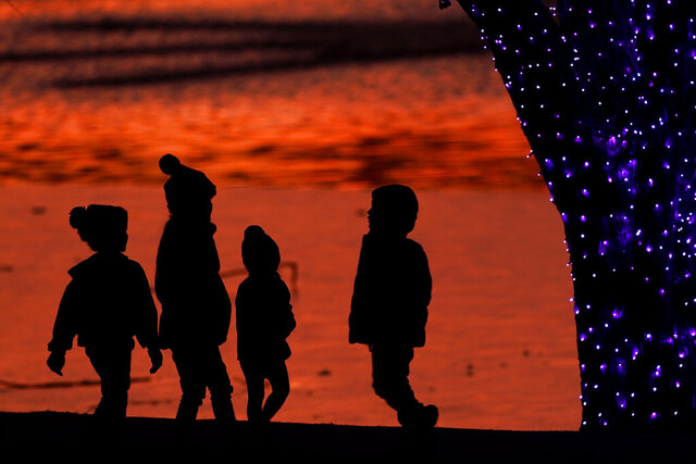 FILE - In this Saturday, Dec. 26, 2020 file photo, children are silhouetted against a pond as they look at Christmas lights at a park in Lenexa, Kan.  Balancing checkbooks and paying in cash are out, credit cards and digital wallets are in. When today's kids grow up, they'll pay for things very differently than their parents and grandparents did. That's why it's important for parents to update the way they teach their children about money management.  (AP Photo/Charlie Riedel, File)