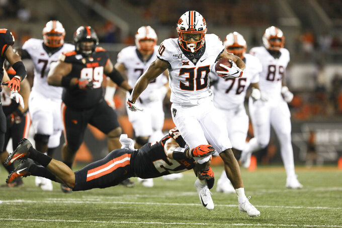 CORRECTS TO CHUBA HUBBARD, INSTEAD OF GABE SIMPSON - Oklahoma State running back Chuba Hubbard (30) is brought down by Oregon State defensive back David Morris (24) during the first half of an NCAA college football game in Corvallis, Ore., Friday, Aug. 30, 2019. (AP Photo/Amanda Loman)