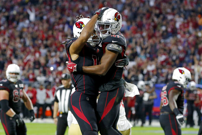 Arizona Cardinals running back Kenyan Drake celebrates his touchdown against the San Francisco 49ers with wide receiver Larry Fitzgerald, left, during the first half of an NFL football game, Thursday, Oct. 31, 2019, in Glendale, Ariz. (AP Photo/Rick Scuteri)