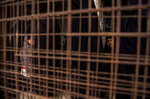 Two young girls are seen through a metal barrier, at al-Hol, which houses families of members of the Islamic State group, in Hasakeh province, Syria, Saturday, May 1, 2021.   It has been more than two years that some 27,000 children have been left to languish in al-Hol camp, which houses families of IS members.   Most of them not yet teenagers, they are spending their childhood in a limbo of miserable conditions with no schools, no place to play or develop and seemingly no international interest in resolving their situation.   (AP Photo/Baderkhan Ahmad)