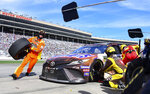 Crew members tend to Kyle Busch's car during a pit stop in a NASCAR Monster Energy NASCAR Cup Series auto race at Atlanta Motor Speedway, Sunday, Feb. 24, 2019, in Hampton, Ga. (AP Photo/Scott Cunningham)