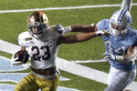Notre Dame running back Kyren Williams (23) runs while North Carolina linebacker Jeremiah Gemmel (44) misses the tackle during the second half of an NCAA college football game in Chapel Hill, N.C., Friday, Nov. 27, 2020. (AP Photo/Gerry Broome)