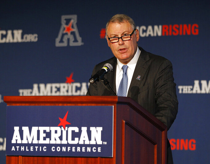 """FILE - In this Aug. 4, 2015, file photo, American Athletic Conference Commissioner Mike Aresco addresses the media during an NCAA college football media day in Newport, R.I. Aresco vehemently denied that his league has ever """"plotted"""" with ESPN to undermine another conference by poaching its schools. Aresco addressed conference realignment Wednesday, Aug. 4, 2021, during the AAC's virtual football media day, saying the league is not actively looking to add schools. (AP Photo/Stew Milne, File)"""