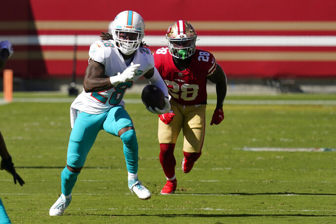 Miami Dolphins strong safety Bobby McCain, left, runs after intercepting a pass in front of San Francisco 49ers running back Jerick McKinnon during the first half of an NFL football game in Santa Clara, Calif., Sunday, Oct. 11, 2020. (AP Photo/Tony Avelar)